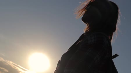 Portrait of the young woman at the background of the sunset. Wind is blowing. Wideo