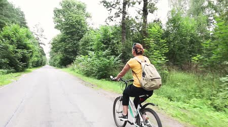 A young woman with a backpack rides a bicycle. An empty road at the forest.