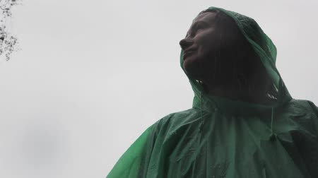A young woman in a green raincoat is standing in the rain in the forest. Enjoying. Wideo