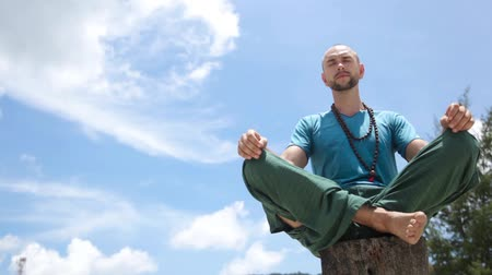 Young male yogi meditating with closed eyes on the background of the blue sky. Wideo