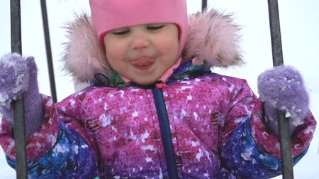 joyfulness : A cute little baby is swinging on a swing, smiling and putting out her tongue on a winter day. The child is dressed in bright winter clothes. Stock Footage