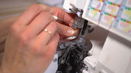 stroj : The tailor changes the needle in the overlock. Close up. Slow motion.