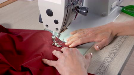 цвет бордо : The tailor completes sewing on an industrial sewing machine. In the hands of the seamstress a cloth with the color of a marsala (bordeaux).