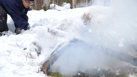 extinguishing : 14-year-old boy putting out the fire with snow. In the background a snow-covered forest.