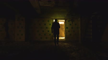 lasca : A man walks with a flashlight through a gloomy, ruined building.