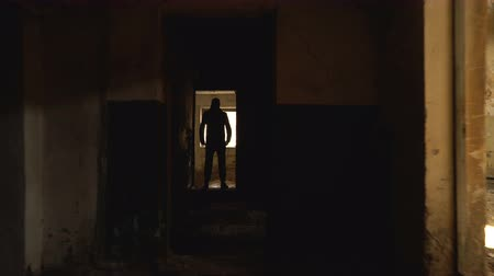 guarda costas : The imaginary man is moving along the corridor of the dark abandoned building. In the doorway is the silhouette of a man.