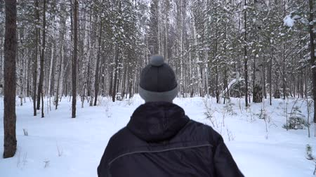 pletený : The runner is surrounded by a birch forest. He is dressed in a black anorak and a gray knitted hat.