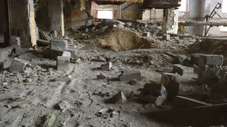 lasca : A fictitious person walks through a destroyed building. The floor is strewn with bricks.