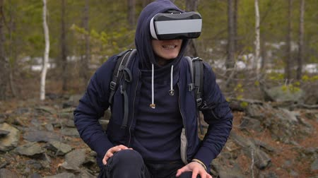 есть : A tourist with a backpack on his back sits on the stones in virtual reality glasses, opens his mouth and shows his teeth. In the background there is a coniferous forest with stony soil.