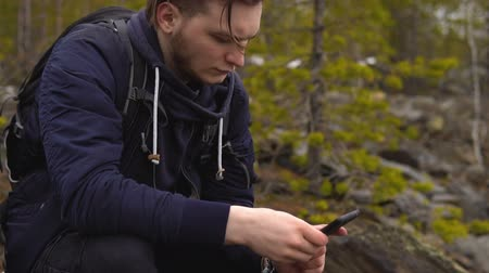 communion : A young tourist with a backpack on his back sits and pokes his finger in the mobile phone screen. In the background there is a coniferous forest with stony soil.