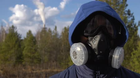 respirator : A young man is standing in a respirator and glasses. In the background, a forest, clouds and a smoking factory pipe. Stock Footage