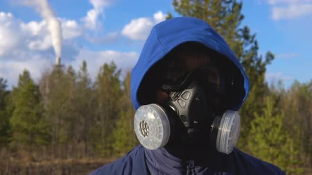 stalker : A young man is standing in a respirator and glasses. In the background, a forest, clouds and a smoking factory pipe. Stock Footage