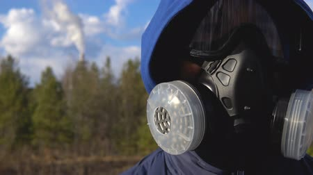 respirator : A young man is standing in a respirator and glasses. In the background, a forest, clouds and a smoking factory pipe. Close up.