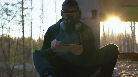 respirator : A young man sits in a ruined building in a respirator and glasses. He holds a tablet and a stylus. In the background trees and sunset. The concept of ecological disaster and post-apocalypse.