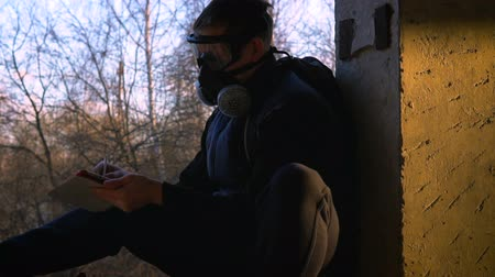 stalker : A young man sits in a ruined building in a respirator and glasses. He holds a tablet and a stylus. In the background trees. The concept of ecological disaster and post-apocalypse.