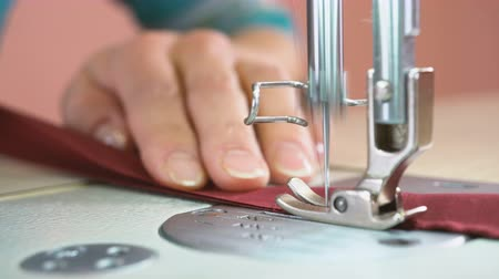 цвет бордо : The tailor sews on an industrial sewing machine. In the hands of the seamstress a cloth with the color of a marsala (bordeaux). Close up. Стоковые видеозаписи