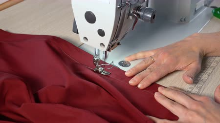 шов : The tailor sews on an industrial sewing machine. In the hands of the seamstress a cloth with the color of a marsala (bordeaux). Fast motion.