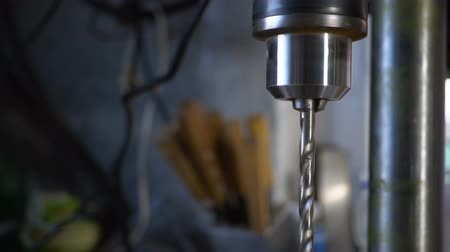 stroj : The movement of the pulley and the drill of the drilling machine on a dark background. Slow motion
