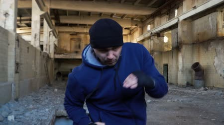 construção muscular : A fight with a shadow. A boxer in a blue sweatshirt trains in an abandoned building. Slow motion.