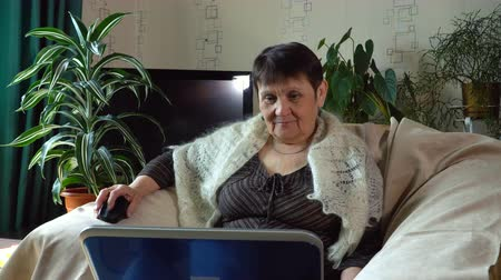 серьги : An elderly woman is sitting in a armchair with a laptop on her lap and smiling. Стоковые видеозаписи