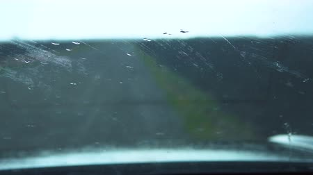 wiper : Wipers wash the raindrops on the windshield of the car. View from inside the car on the field.