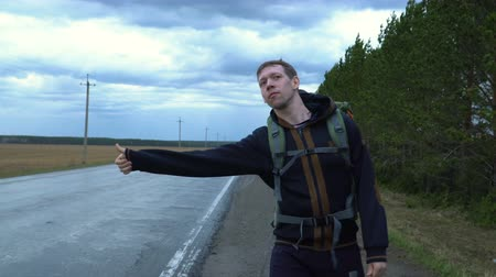 liften : A tourist hitchhiker walks along the road with a backpack on his shoulders, lifting his thumb up. Traveler is trying to stop the car. The weather is cloudy and rainy.