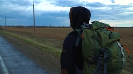 távolság : A tourist hitchhiker walks along the road with a backpack on his shoulders. The weather is cloudy and rainy. Stock mozgókép