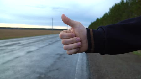 liften : A tourist hitchhiker walks along the road with a backpack on his shoulders, lifting his thumb up. Traveler is trying to stop the car. The weather is cloudy.