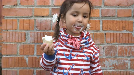 ワッフル : Cute little girl is eating ice cream on a brick wall background. 動画素材