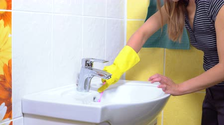 escova de dentes : A woman is cleaning a sink with a toothbrush in the bathroom.
