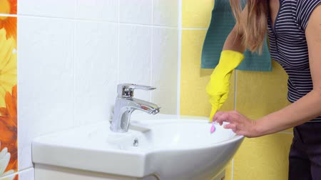 dezenfekte etmek : A woman is cleaning a sink with a toothbrush in the bathroom.