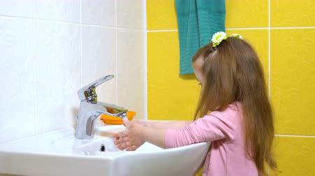 mycie rąk : A three-year-old girl washes her hands and wipes them with a towel.