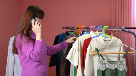 ruhakészítés : A woman talks on her mobile phone and looks at the clothes in the dressmaking studio.