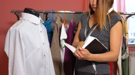 varrónő : The tailor takes measurements against the background of clothes hangers.