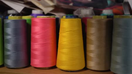 spool : The seamstress takes the spool of pink thread from the shelf.