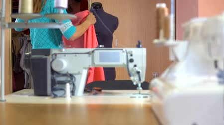 шитье дамского платья : A tailor woman takes a cloth in a closet and tries it on a dummy in sewing studio.