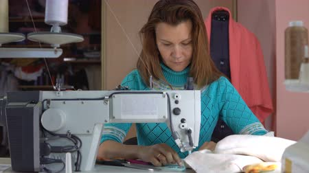só as mulheres jovens : A tailor woman sews on an industrial sewing machine.