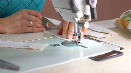 szervezett : The tailor sews on an industrial sewing machine. In the hands of the seamstress a jacquard cloth. Close up.