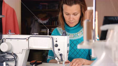 cuciture : The tailor sews on an industrial sewing machine in sewing studio. Filmati Stock