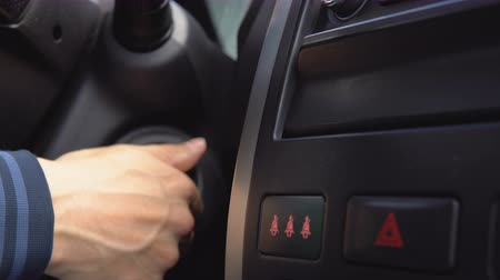 switch : Male hand starting a car engine with ignition key. Close up. Stock Footage