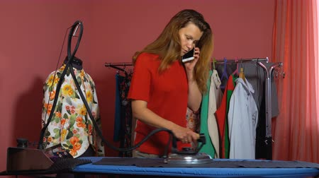 varrónő : A young woman tailor ironing a gray cloth and talking on the mobile phone. In the background a mannequin and hangers with things.