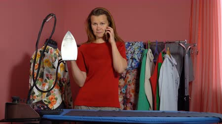 vállfa : A young woman tailor ironing a gray cloth and talking on the mobile phone. In the background a mannequin and hangers with things.