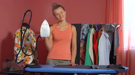 varrónő : A woman tailor holds an iron in her hand and smiles. In the background a dummy and hangers with things.