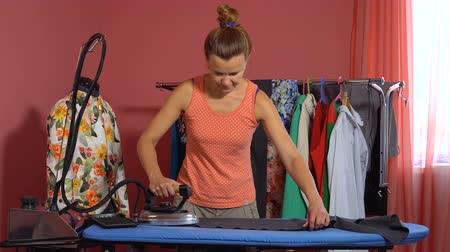 žehlení : A tailor woman is ironing a gray cloth on the ironing board. In the background a dummy and hangers with things.