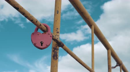 bağlılık : Heart shaped padlock on metal railing of bridge. Stok Video