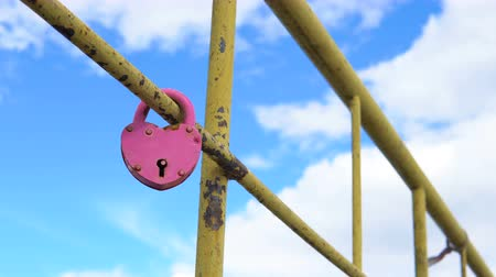hűség : Heart shaped padlock on metal railing of bridge. Stock mozgókép