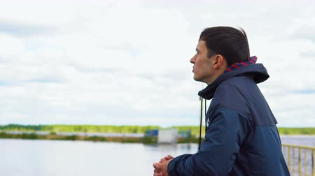 looking distance : A young man is standing on a bridge next to the river and looking into the distance. In the background, the forest and the cloudy sky. Stock Footage
