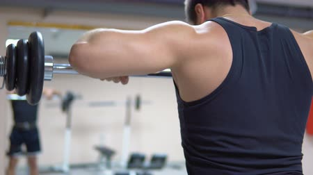 hand on chin : A man in black clothes is training with a barbell in the gym. Deltoid muscles training. Thrust rod to the chin. View from the back.