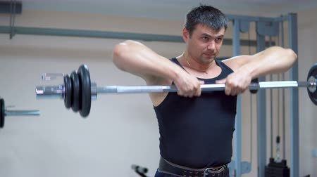 hand on chin : A man in black clothes is training with a barbell in the gym. Deltoid muscles training. Thrust rod to the chin.