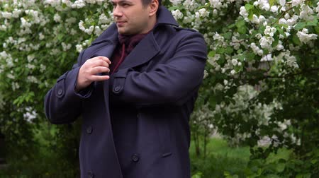 фон : A man in a black coat is looking for a cell phone in his inner pocket. In the background are blooming apple trees.